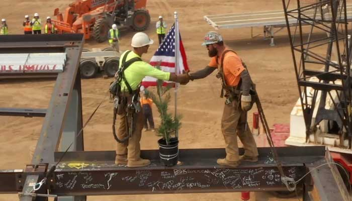 Construction workers shaking hands atop final beam