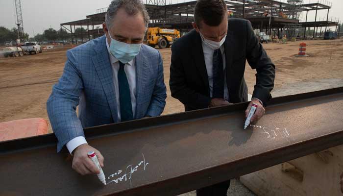 Executives signing final beam